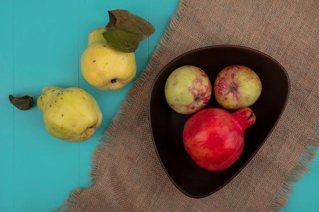 Draufsicht des frischen granatapfels mit äpfeln auf einer schüssel auf einem sackstoff mit quitten lokalisiert auf einem blauen hintergrund