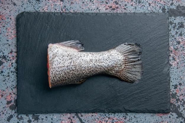 Draufsicht des frischen rohen fisches auf dunklem farbtablett auf blau-schwarzer mischfarbtabelle