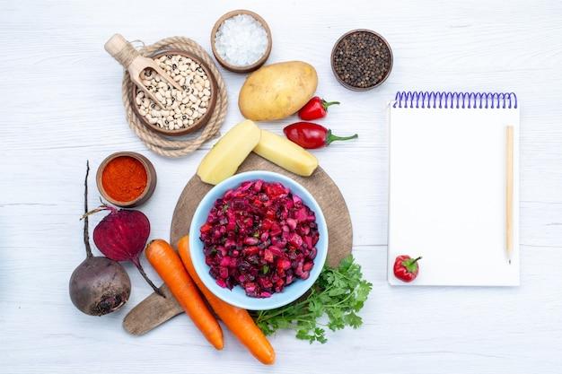 Draufsicht des frischen rübensalats mit geschnittenem gemüse zusammen mit rohen bohnen karottenkartoffeln notizblock auf hellem schreibtisch, lebensmittel mahlzeit gemüse frischer salat