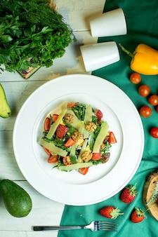 Draufsicht des frischen salats mit parmesankäse-walnuss-kirschtomaten und erdbeeren in einer weißen schüssel