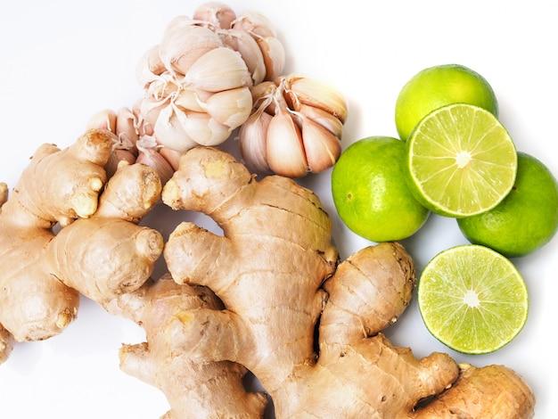 Draufsicht des frischgemüses oder der kräuter mit der ingwerwurzel-, knoblauch- und zitronenkalkzitrusfrucht lokalisiert auf weißer oberfläche.