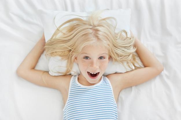 Draufsicht des fröhlichen kleinen mädchens mit den blonden haaren, den fackeln und den blauen augen, die gestrippte pyjamas tragen, die auf weißem kissen und leinen in ihrem bett liegen, spaß haben und lachen, wollen tagsüber kein nickerchen machen