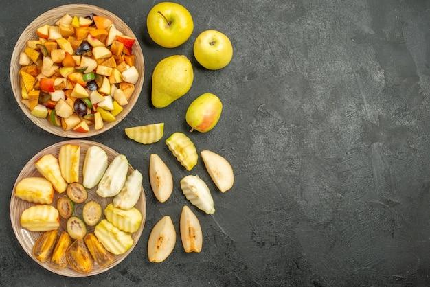 Draufsicht des fruchtigen salats mit frisch geschnittenen früchten auf dem dunklen hintergrund