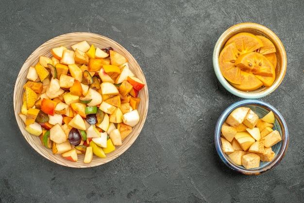Draufsicht des fruchtigen salats mit geschnittenen früchten auf grauem hintergrund