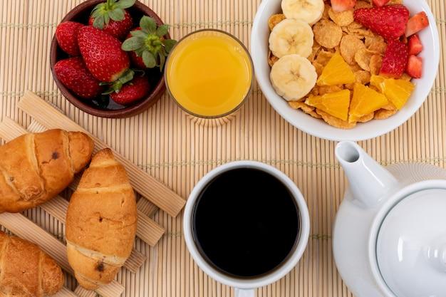 Draufsicht des frühstücks mit cornflakes, erdbeeren, saft und croissants auf der horizontalen strohoberfläche