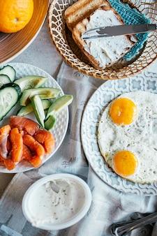 Draufsicht des frühstücks mit käse des eies, des lachses, der avocado, der gurke und des gegrillten brotes mit sahne. hausgemachtes essen. norwegen frühstück.