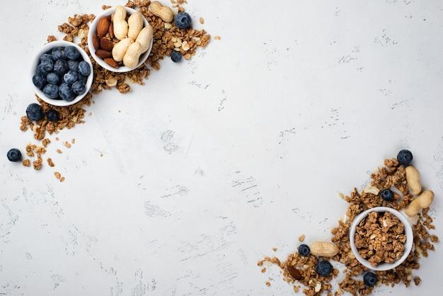 Draufsicht des frühstückskost aus getreide in den schüsseln mit blaubeeren und zusammenstellung von nüssen