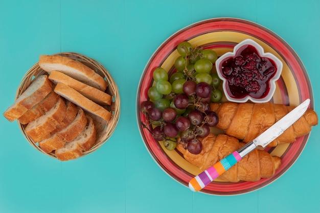 Draufsicht des frühstückssatzes mit croissant-trauben-himbeermarmelade und brotscheiben mit messer auf blauem hintergrund