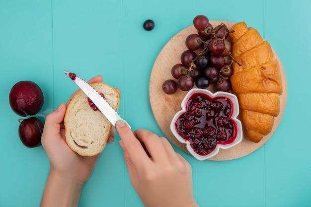 Draufsicht des frühstückssatzes mit croissant- und himbeermarmeladentraube auf schneidebrett und weiblicher hand, die marmelade auf brot und pluots auf blauem hintergrund ausbreitet