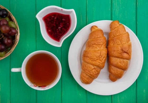 Draufsicht des frühstückssatzes mit croissants in teller tasse tee himbeermarmelade in schüssel und korb von traubenschleifenbeeren auf grünem hintergrund