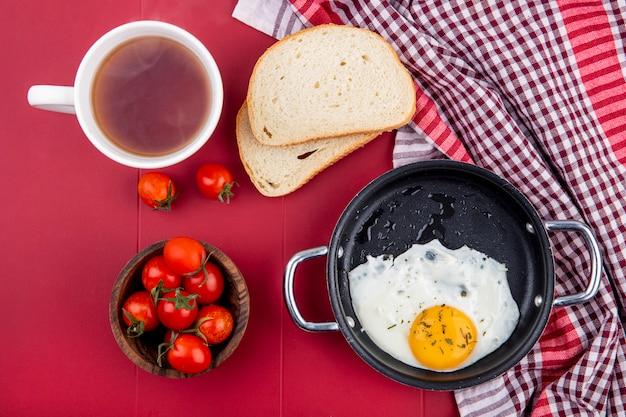 Draufsicht des frühstückssatzes mit pfanne des spiegeleis und schüssel tomatenbrotscheiben auf kariertem stoff und tasse tee auf rot