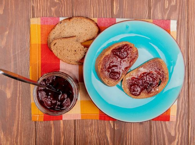 Draufsicht des frühstückssatzes mit roggenbrotscheiben, die mit marmelade in teller- und erdbeermarmeladen-roggenbrotstücken auf kariertem stoff und holztisch verschmiert wurden