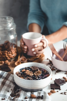 Draufsicht des frühstückstisches mit kaffee, müsli, nüssen, beeren und milch