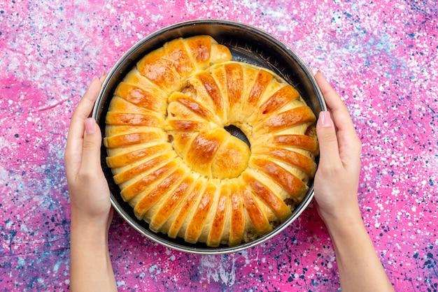 Draufsicht des gebackenen gebäck köstlichen armreifs gebildet innerhalb der pfanne auf hellem schreibtisch, gebäckkekskeksteig süßer zucker