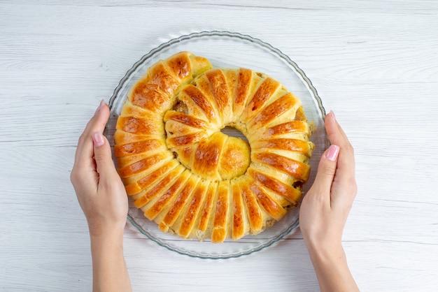 Draufsicht des gebackenen leckeren gebäckarmreifs gebildet innerhalb platte auf hellem schreibtisch, gebäckkeks süßer auflauf