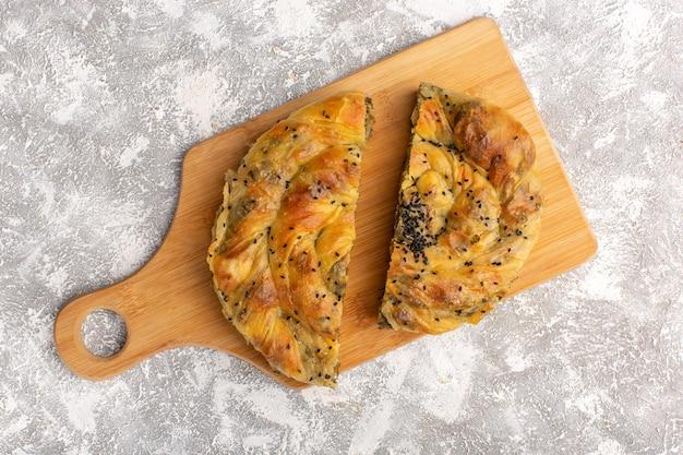 Draufsicht des gebäcks mit fleisch köstliche teigmahlzeit geschnitten auf weißer heller oberfläche