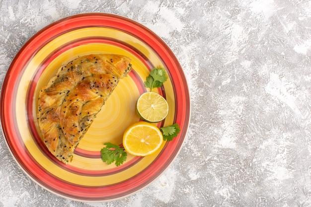 Draufsicht des gebäcks mit fleisch köstliche teigmahlzeit innerhalb platte geschnitten mit zitrone auf hellweißer oberfläche