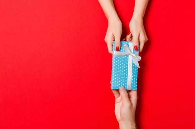 Draufsicht des gebens und empfangens eines geschenks auf der bunten oberfläche. in männlichen und weiblichen händen vorhanden. liebeskonzept. speicherplatz kopieren.