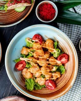 Draufsicht des gebratenen huhns mit tomaten und soße auf salat auf einem teller auf rustikalem