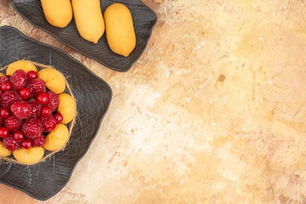 Draufsicht des gedeckten tisches mit einem geschenkkuchen für gäste auf gemischtem farbtisch