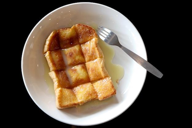 Draufsicht des gegrillten brotes mit butter und versüßter kondensmilch