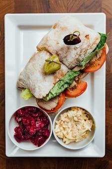 Draufsicht des gegrillten hühnersandwiches gemacht mit selbst gemachtem brot, tomate und kopfsalat.