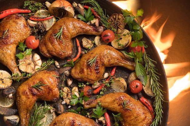 Draufsicht des gegrillten hühnerschenkels mit verschiedenem gemüse auf pfanne auf dem brennenden grill