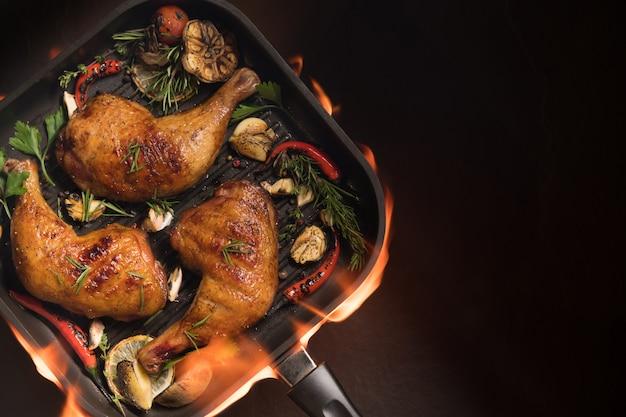 Draufsicht des gegrillten hühnerschenkels mit verschiedenem gemüse auf pfanne auf dem flammenden grill auf schwarzem hintergrund