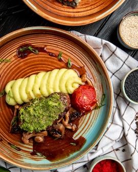 Draufsicht des gegrillten rindfleischs mit kartoffelpüree tomatenpilzen und avocadosauce in einem teller auf holz