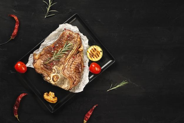 Draufsicht des gegrillten t-bone-steaks auf schwarzem tisch