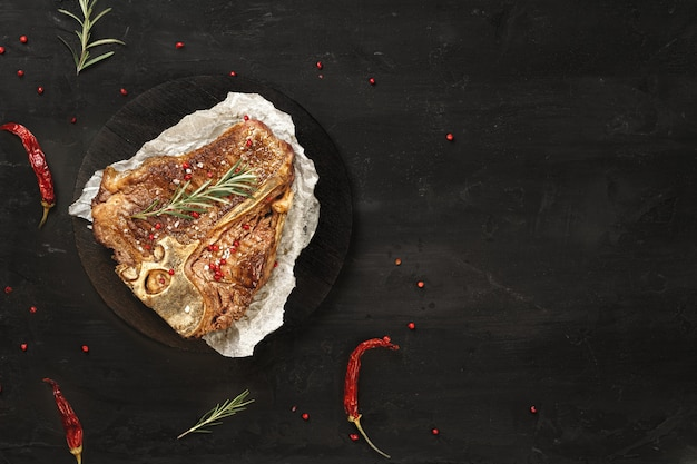 Draufsicht des gegrillten t-bone-steaks mit gewürzen auf schwarzem tisch