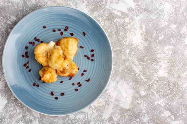 Draufsicht des gekochten blumenkohls innerhalb der blauen platte auf weißlichtoberfläche