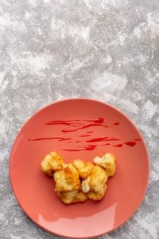 Draufsicht des gekochten blumenkohls innerhalb der pfirsichplatte auf der hellen oberfläche