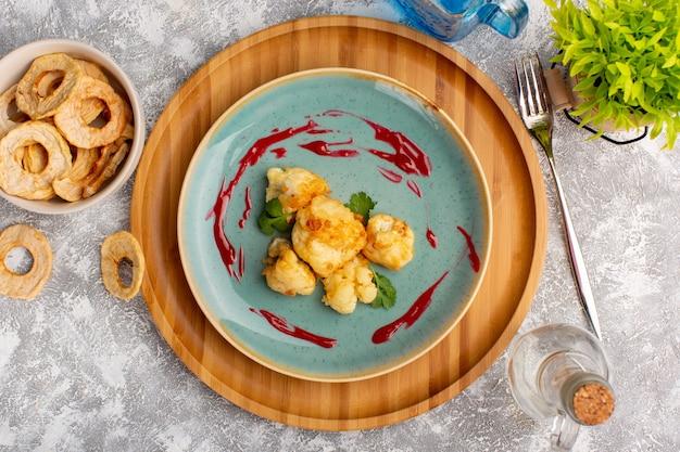 Draufsicht des gekochten geschnittenen blumenkohls innerhalb der blauen platte auf der weißen oberfläche