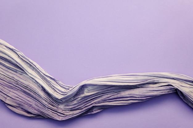 Draufsicht des gekräuselten stoffes auf lila hintergrund. feine glänzende seide oder synthetischer stoff mit gestochen scharfer textur, kopierraum für kreatives modedesign, tapeten, postkarten