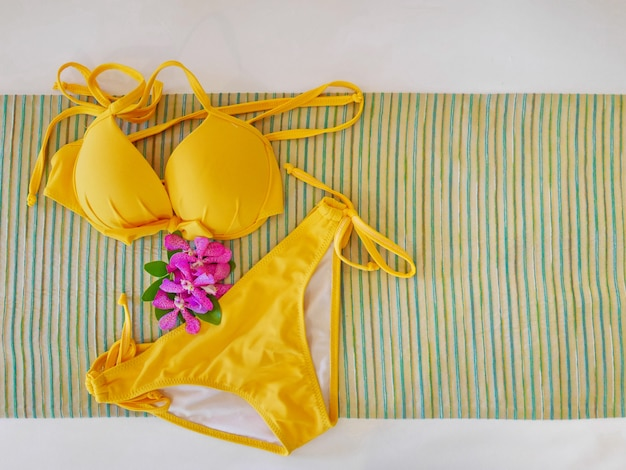 Draufsicht des gelben bikinis mit purpurroter orchidee auf abstraktem gewebe