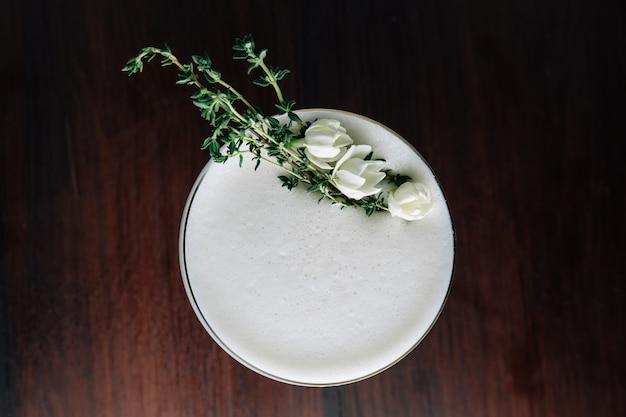 Draufsicht des gelben cocktails mit weißem schaum verziert mit weißer blume und grüner niederlassung.