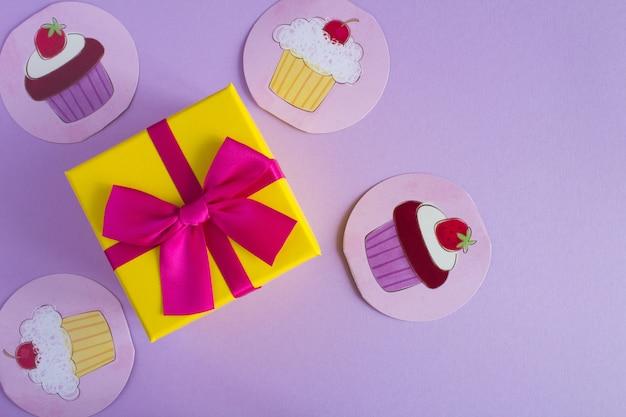 Draufsicht des gelben geschenks mit einer rosa schleife und gezeichneten cupcakes auf dem veilchen