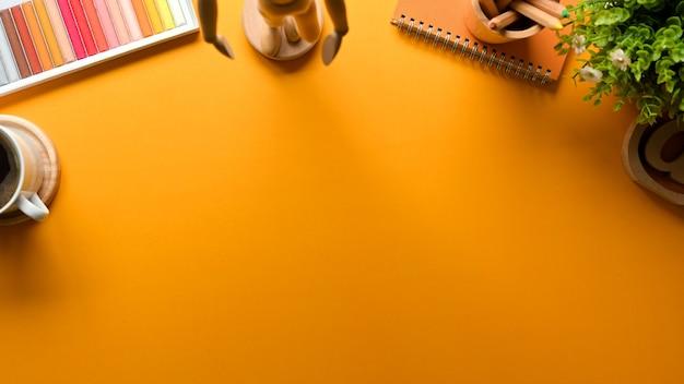 Draufsicht des gelben kreativen flachen laienarbeitsbereichs mit buntstiftdekorationen und kopierraum
