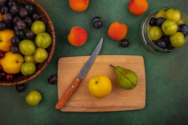 Draufsicht des gelben pfirsichs auf einem hölzernen küchenbrett mit grüner birne mit messer auf grünem hintergrund