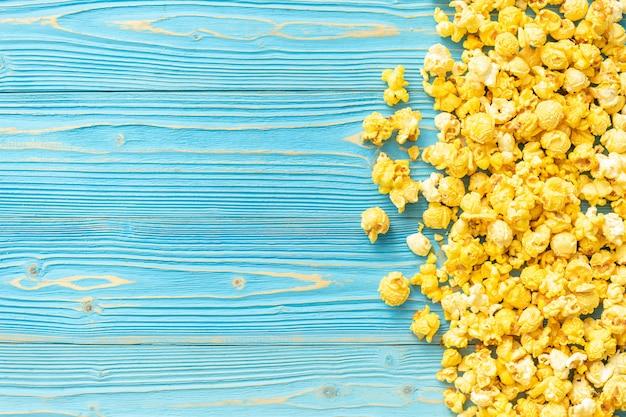 Draufsicht des gelben popcorns auf blauen hölzernen planken