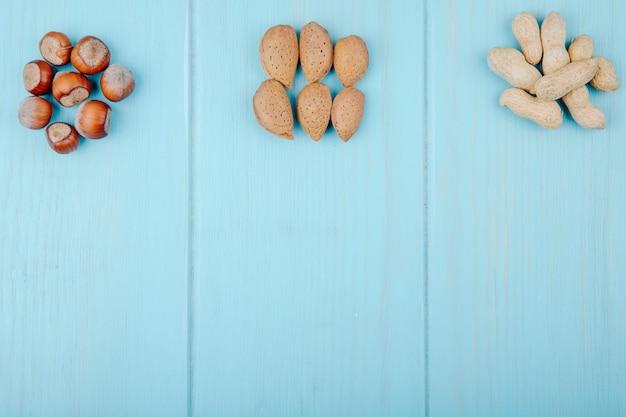 Draufsicht des gemischten nusshaufens lokalisiert auf mandeln des blauen hintergrundes haselnüsse und erdnüsse mit kopienraum