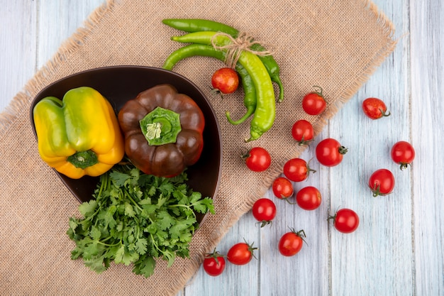 Draufsicht des gemüses als bündel korianderpfeffer in der schüssel und auf sackleinen mit tomaten auf holzoberfläche