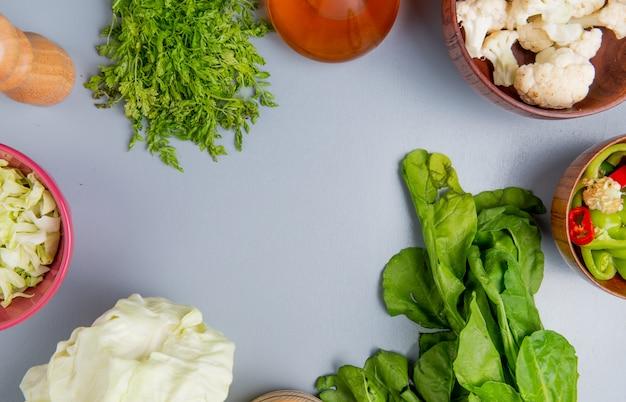 Draufsicht des gemüses als ganzes und geschnittenes kohlspinat-bündel koriander-blumenkohl- und pfefferscheiben mit geschmolzener butter und salz auf blauem hintergrund