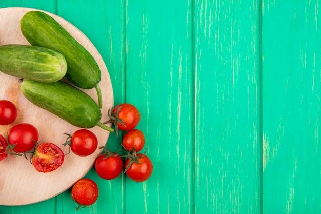 Draufsicht des gemüses als gurke und tomate auf schneidebrett auf grüner oberfläche