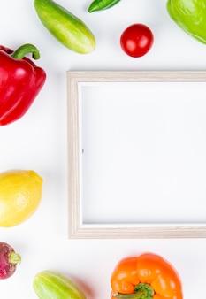 Draufsicht des gemüses als pfeffer-gurken-rettich-tomate mit rahmen auf weißer oberfläche mit kopienraum