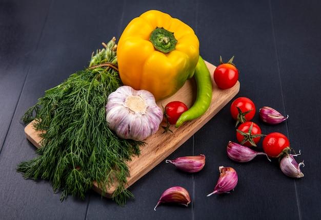 Draufsicht des gemüses als pfeffer-tomaten-knoblauchknollen-dillbündel auf schneidebrett mit knoblauchzehen auf schwarzer oberfläche