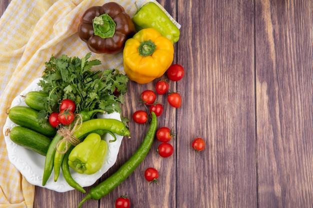 Draufsicht des gemüses als pfefferkoriandergurke im teller auf kariertem stoff mit tomaten auf holzoberfläche