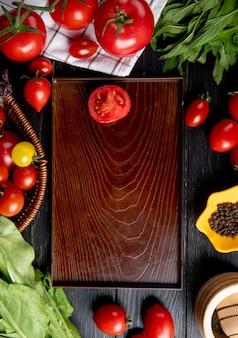 Draufsicht des gemüses als tomatengrünminze verlässt spinat und schneidet tomate in schale auf holz