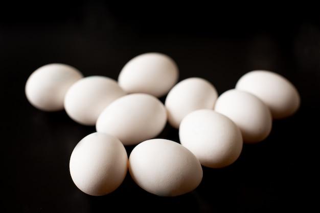 Draufsicht des geöffneten kastens mit eiern auf schwarzem hintergrund.